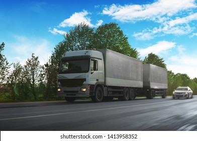 Big truck in motion and white trailer and other car on the countryside road against blue sky with clouds