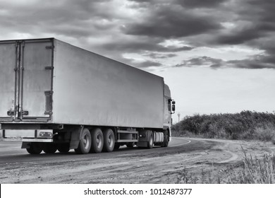 Big truck overtaking a small truck on a road in a rural landscape