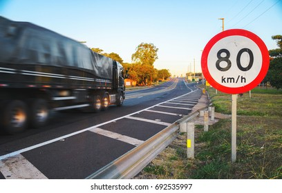 Big truck passing on high speed on the road commenting an infraction by exceeding speed limits. Round speed limit warning board at 80 km per hour.