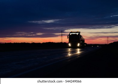 Big truck wagon rides on the road outside the city at sunset and sky with clouds