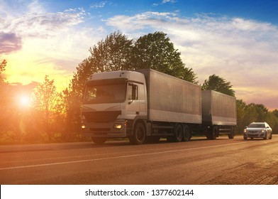 Big truck and white trailer and other car on the countryside road against sky with sunset