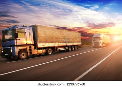 Big trucks in motion and white trailers with space for text on the countryside road against sky with sunset
