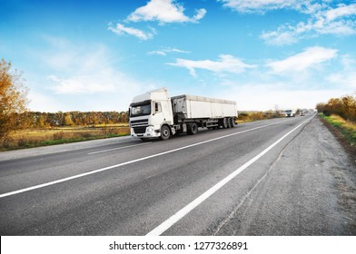 Big trucks and white trailers and cars on the countryside road against blue sky with clouds