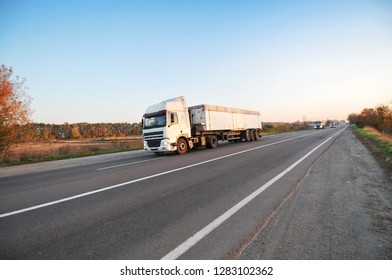Big trucks and white trailers and cars on the countryside road against clear sky