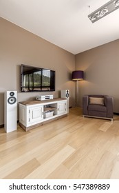 Big TV, home cinema set, cabinet, standing lamp and armchair in spacious modern room