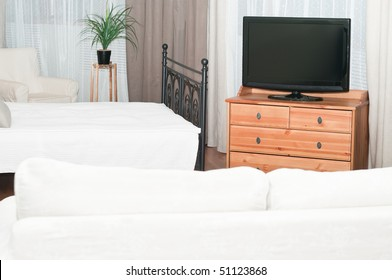 The big TV set in a room before a white sofa. A bedroom with a bed