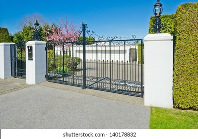 Big two double doors garage with long driveway behind the gates in suburbs of Vancouver, Canada.