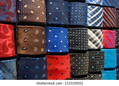Big variety of different color neckties on a shelf in a men clothing store