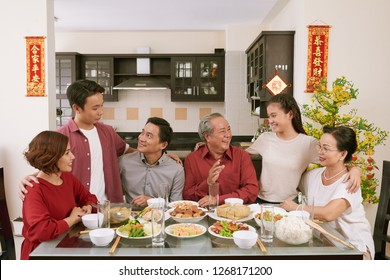 Big Vietnamse family enjoying traditional dinner and celebrating Lunar New Year, couplets with best wishes for coming year in the background