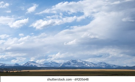 Big view of snowy mountains and vast open space under dramatic clouds near Kenosha Pass, Colorado