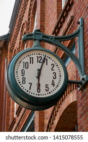 big vintage clock hangs at a red brick facade in Delmenhorst (Germany), it shows three minutes after six