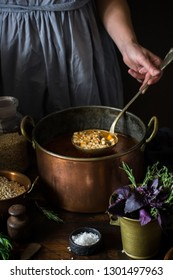 Big vintage copper pan with soup and ladle in female hand. Style rustic. Selective focus.