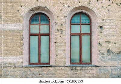 Big vintage rounded building windows on the brick wall. Loft wallpaper. Construction facade concept. Vintage effect.