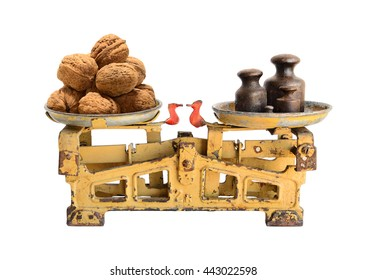 Big walnuts on the old fashioned scales with kettlebells. Isolated on white background