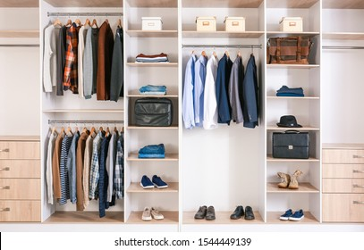 Big wardrobe with clothes in dressing room