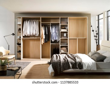 Big wardrobe with different clothes for dressing room with a bed. Interior structure of wardrobe body and shelf design.