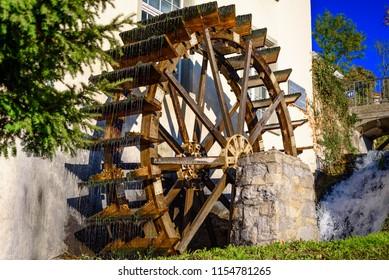 Big water wooden wheel near the house. Water mill on the Rhine waterfall in Switzerland. Swiss landmark on the Rhine river.Water flows on a wooden wheel.
