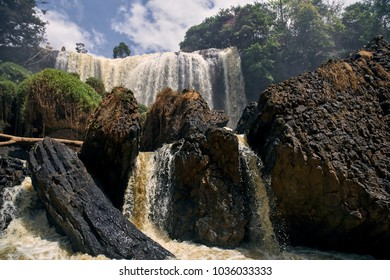 Big waterfall among green vegetation