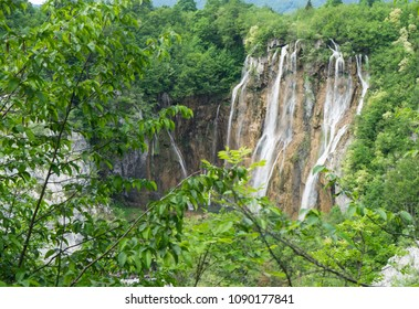 Big waterfall behind the trees at Plitvice Lakes National Park in Croatia
