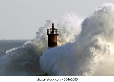 Big wave against lighthouse in the north of Portugal in a stormy overcast evening - mouth of river Ave in Vila do Conde