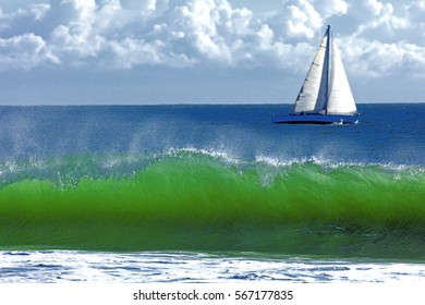 Big wave break spray in the Pacific Ocean and Sailboat