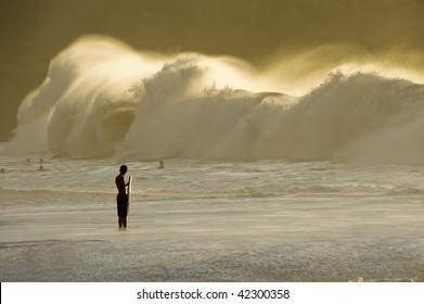 Big wave breaking on the shore. Bodyboarder watching. Waimea Bay, North Shore of Oahu, Hawaii.
