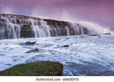 Big wave cause of beautiful scenery of waterfall and water flow at Karang Taraje Bayah Banten Sawarna Beach Indonesia. Soft focus during long exposure shoot.