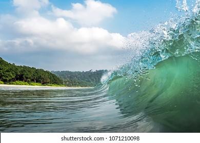 a big wave covers. Radhanagar Beach At Andaman and Nicobar Island, India. view from the sea. bursts of water at sea. The spray of water droplets. under the crest of a wave. crest of wave
