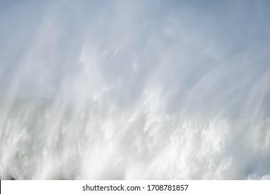 A big wave crashing in the coast. Plenty of blank space.