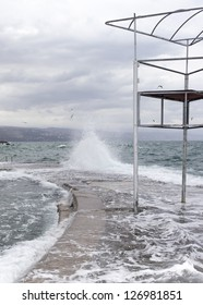 Big wave on stormy day, beating on the seaside resort coast with abandoned baywatch- beach life guard tower