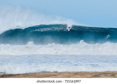 Big wave surfing in Puerto Escondido, Mexico. Surfer riding massive XXL Wave at huge beach break.