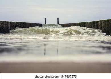 a big wave with whitecaps breaks on the breakwater on a dutch beach.