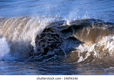 A big waves breaking on a beach with lots of spray and foam.