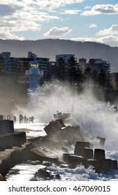Big waves breaking over Wollongong harbor breakwall and lighthouse, Wollongong, New South Wales, Australia. People getting splashed by rough seas.