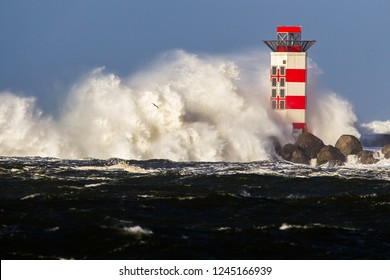 Big waves crashing against the lighthouse at the tip of the pier of Ijmuiden, Netherlands, during severe storm over the North Sea.