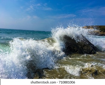 Big waves crashing over rocks at beach.