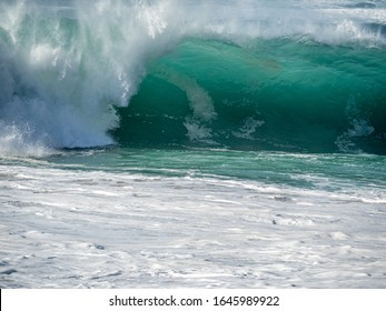 Big waves on the north shore of Oahu with aquamarine seas, white foam and blue skies.