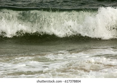 Big waves from the open Atlantic Ocean roll in and crash on the beach of Assateague Island National Seashore in Maryland, USA.