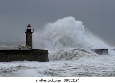 Big waves over pier and lighthouse in a stormy dark morning