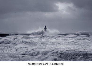 Big waves over piers and lighthouse against a stormy dark cloudy sky. Douro river mouth, Porto, Portugal. Toned blue.