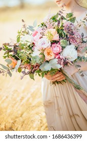 big wedding bouquet in hands of the bride, modern bouquet with a silk ribbons for the bride, summer stylish floristry, the bride in a beige dress holds the flowers