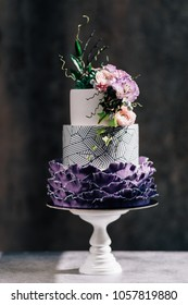 Big wedding cake. Decor trends. Wedding ceremony.Cake with blackberry mousse in the mirror glaze decorated with a molecular biscuit. On the black background.