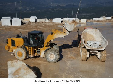 a big whell loader holding marble block in marble quarry