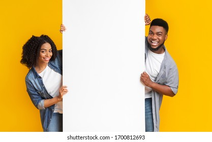 Big White Advertisement Board In Hands Of Smiling Black Couple That Standing On Yellow Background, Copy Space For Your Text, Panorama