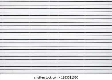 Big white board building from battens. Long white battens pattern. Paneling wall texture. Concept of interior and exterior design, House decoration.