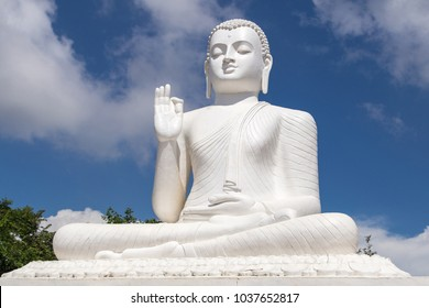 Big white Buddha statue against blue sky in Mihintale, the cradle of buddhism at Sri Lanka