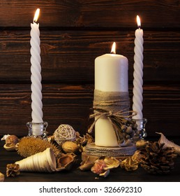 Big white candle and two spiral white candles on rustic wooden background.
