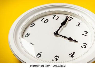 big white clock hanging on a yellow wall