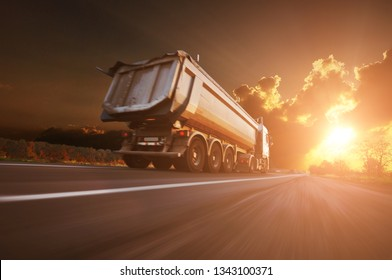 Big white dump truck in motion on the countryside road against night sky with sunset
