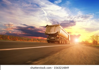 Big white dump truck in motion on the countryside road against a night sky with a sunset